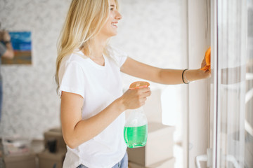 Beautiful woman cleaning window at new home after moving, her husband hanging picture on background