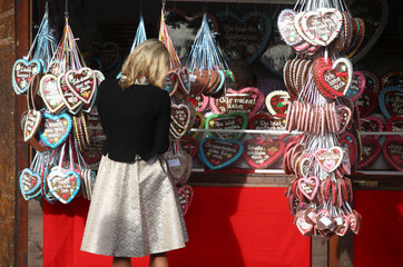 A woman adjusts traditional gingerbread hearts at a booth at the opening day of the 185th Oktoberfest in Munich