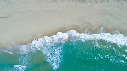 COPY SPACE: Flying above turquoise ocean waves washing the empty sandy beach.