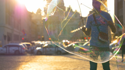 SLOW MOTION: Male street performer making large soap bubbles near the cathedral.