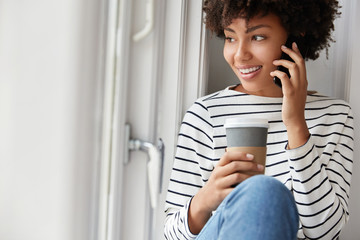 Cropped image of attractive smiling African American woman, has pleasant talk via smart phone during rainy weather, sits on window sill, dressed casually, drinks coffee, enjoys domestic atmosphere