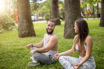 Professional yoga trainer and his female student conduct their outdoor training in a green city park. The concept of a healthy lifestyle.