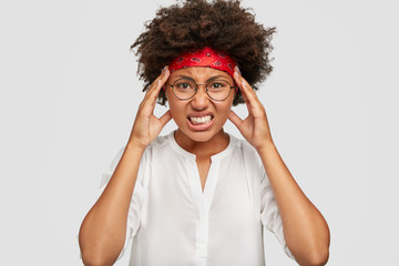 Stressful black girl has terrible headache, touches head with hands, clenches teeth, has Afro hairstyle, cant concentrate on something, poses against white background. Negative feeling concept