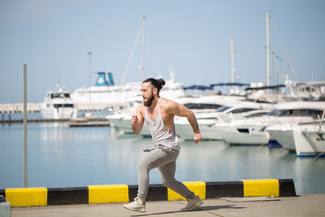 Caucasian sportsman jogging on ocean pier or waterfront with anchored yachts, working out in summer morning.