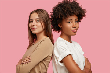 Diversity and feminity concept. Confident young mixed race women stand backs to each other, keep hands crossed over chest, collaborate for common task, dressed casually, isolated over pink background.