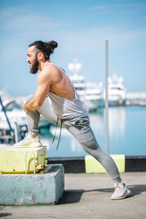 Athletic bearded sportsman with trendy hairstyle stretching legs while standing at the sea pier with sailing boats on background