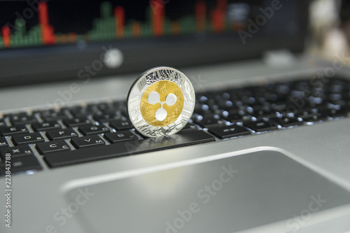 Golden And Silver Ripple Coin On A Black Keyboard Of Silver Laptop