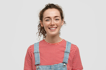 Horizontal shot of happy freckled woman adult with curly hair, pleasant smile, looks happily at camera, wears striped t shirt and denim dungarees, isolated over white background. Youth concept