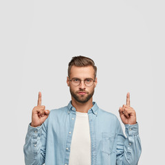 Photo of unshaven hipster dressed in casual shirt, points with both index fingers upwards. shows free space for your promotional content or advertisement. Lets go upstairs. Indoor vertical shot
