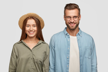 Isolated shot of happy friends enjoy pastime together, have toothy smiles, rejoice positive moments, stand closely against white studio wall. Glad woman in straw hat and her boyfriend have date