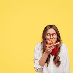 Pleasant looking female enjoys delicious slice of pizza, being hungry, looks with dreamy expression upwards, likes this taste, wears eyewear and white oversized shirt, stands against yellow background
