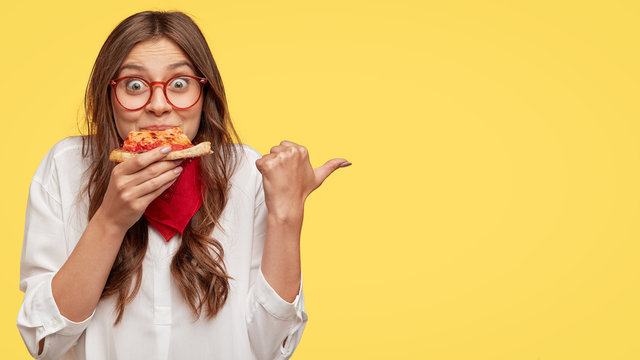 Lunch time concept. Attractive cheerful woman eats delicious Italian pizza, surprised with wonderful taste, indicates with thumb aside, shows where pizzeria situated, suggests to visit and have snack