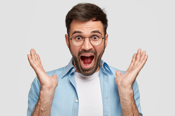 Surprised young amazed man with stubble opens mouth widely, clasps hands near face, wears glasses for good vision, hears unexpected positive news, isolated over white background. Emotions concept