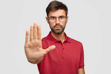 Concerned serious bearded man in round eyewear pulls palm towards camera, stops or warns you from making bad choice, shows enough or rejection gesture, isolated on white wall. Slow down, please!