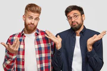 Hesitant bearded brothers clasp hands with puzzlement and bewilderment, stand next to each other, feel clueless concerning something, dressed in fashionable clothes, isolated over white background