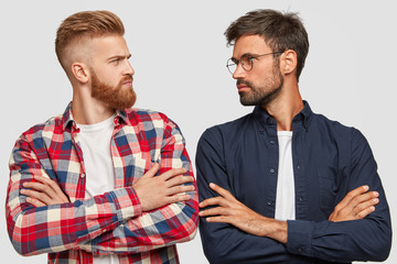 Photo of serious male opponents stand crossed hands, look at each other, have competiton, stand shoulder to shoulder against white background, ready to rival. People and relationships concept
