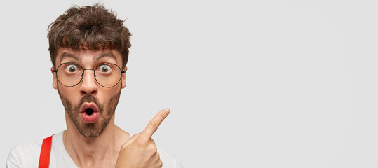 Emotive hipster with surprised expression, gasps from wonder, indicates at copy space with index finger, shows free space for your promotion, wears round transparent glasses. Advertisement concept