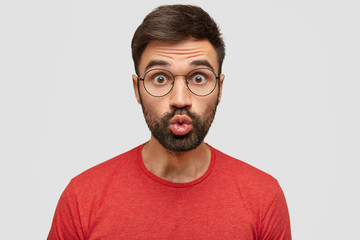 Attractive funny man with surprised expression keeps lips rounded, sends kiss, wears spectacles, dressed in casual red t shirt, poses against white background. Facial expressions, masculinity