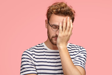 Tired overworked curly ordinary man keeps hand on face, closes eyes, feels sleepy after working all night, dressed in striped t shirt, isoated over pink studio wall. Fatigue freelancer needs rest. Wall mural