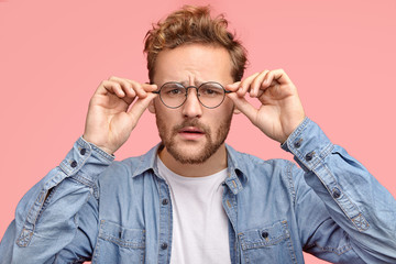 Horizontal shot of pleasant looking guy looks scrupulously through glasses, tries to notice something, has bad sight, dressed in fashionable shirt, poses against pink studio wall. Facial expressions