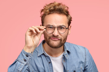 Headshot of mysterious European young boyfriend pouts lips at camera, wears round transparent glasses, has intriguing look at camera, dressed in fashionable shirt, isolated over pink background