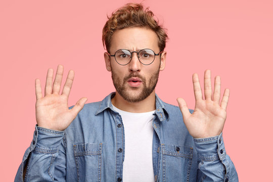Calm down, please! Handsome unshaven Caucasian man keeps palms in front, asks to leave him in peace and not interrupt, has indignant facial expression, poses against pink background, gestures indoor