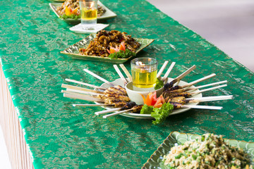 Chicken Satay grilled on Bamboo Sticks, typical Thai or Indonesian Food