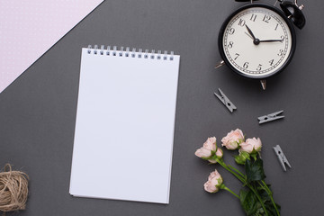 White notepad with flowers and alarm clock on grey background in vintage style top view