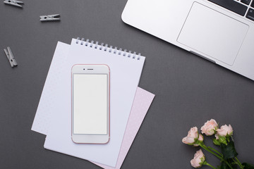 Phone with empty screen with paper and flowers on grey background in vintage style