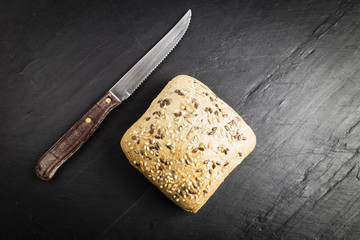 Bread with linseed, oats and sesame seeds next to a knife on a black chalkboard