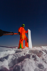 Snowboarder making a selfie by his action camera on the top of the ski slope