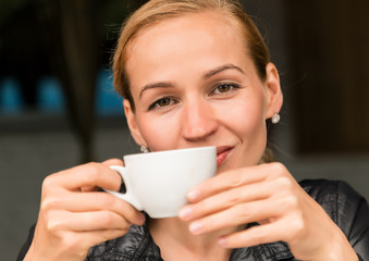 Young beautiful woman with a cup of coffee in a outdoor cafe, girl have a lunch on terrace