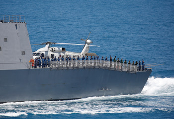 Crew members of Japanese destroyer Suzutsuki wave to a Japanese helicopter carrier Kaga after their joint naval drill with Indonesian patrol boat Kurau in the Indian Ocean