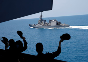 Crew members of Japanese helicopter carrier Kaga wave to Japanese destroyer Suzutsuki after its joint naval drill with Indonesian patrol boat Kurau in the Indian Ocean