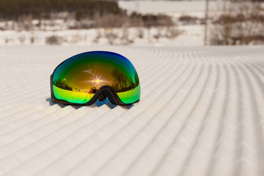 Ski goggles laying on a new groomed snow and empty ski slope