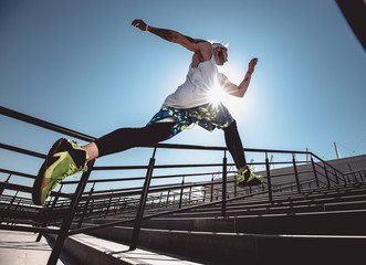 Handsome young muscular man in modern sport clothing run up the stairs outdoor at bright sunny day. Wide angle photo of a jogging man. Sport lifestyle