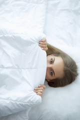 Face closeup of a beautiful young woman hiding her face under the sheet
