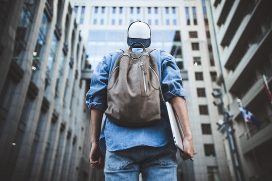 Cheerful young man with backpack enjoying walk the city with laptop and snap back.