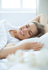Beautiful young blonde woman sleeping in bed