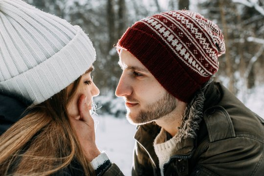 happy young people, couple in winter snowy forest. beautiful lovers having fun.