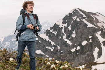 cheerful backpacker is holding his digital camera while standing on the hill with magnificent landscape on the background