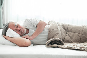 Senior man sleeping in bed.