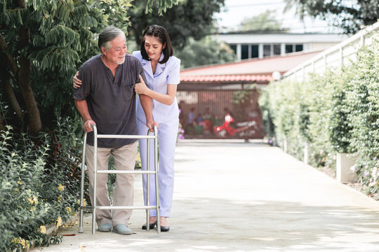 Nurse with patient using walker in retirement home.