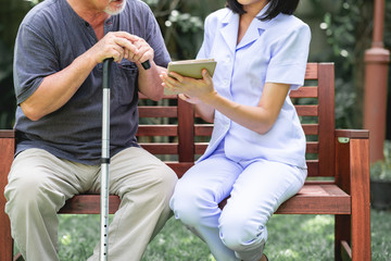 Nurse with patient sitting on bench together looking at tablet.
