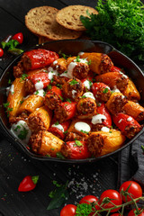 Sausage meat, mince and rice Stuffed sweet mini bell peppers baked in cast iron skillet, pan topped with yogurt and fresh parsley