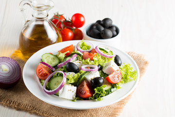 Fresh Greek salad made of cherry tomato, ruccola, arugula, feta, olives, cucumbers, onion and spices. Caesar salad in a white bowl on wooden background. Healthy organic diet food concept.