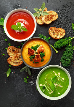 Variety of cream soup bowls: sweet pea and mint, tomato and basil and butternut squash with steamed kale and fried halluomi