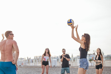 young people group have fun and play beach volleyball at summer day