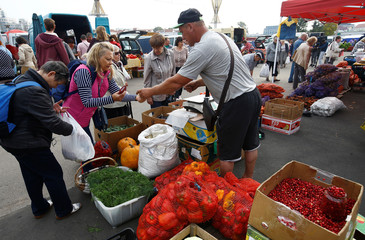 People buy vegetables at a market during the annual autumn agriculture fair in Minsk