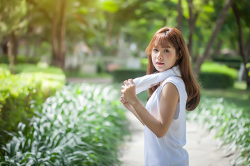 Beautiful young woman with happy morning exercise in the park. Looking at camera.